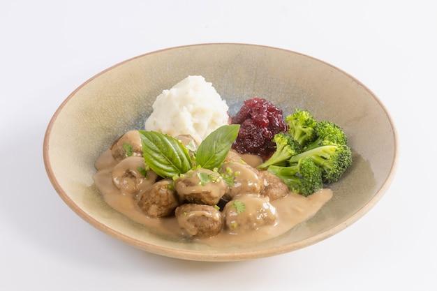 Almôndegas suecas com molho cremoso, purê de batata e molho de mirtilo.