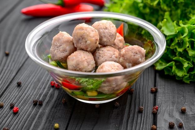 Almôndegas tradicionais com carne de frango com caldo de galinha, em superfície preta Foto Premium