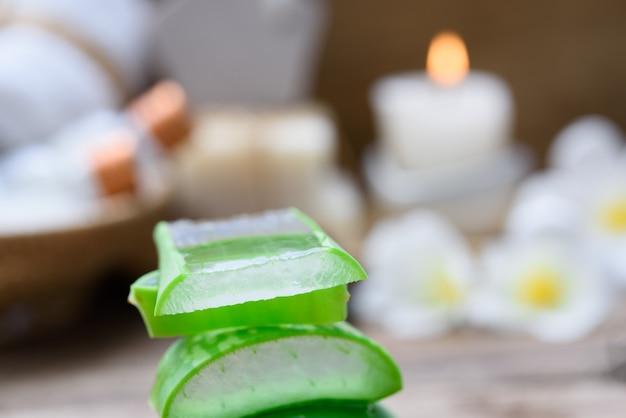 Alo vera fatiado, produtos de tratamento e tratamento de spa com flores, sabonete, toalha e ervas bola na mesa de madeira rústica, foco seletivo