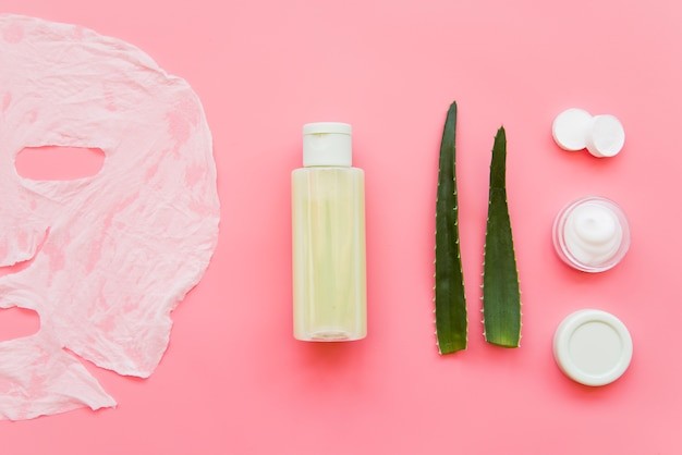 Aloe vera creme hidratante para a pele; loção e máscara de folha de papel no pano de fundo rosa
