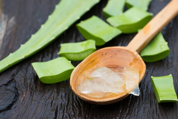 Aloe vera gel na colher de pau com aloe vera na mesa de madeira