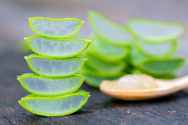 Aloe vera na colher de pau na mesa de madeira existem muitas ervas úteis.