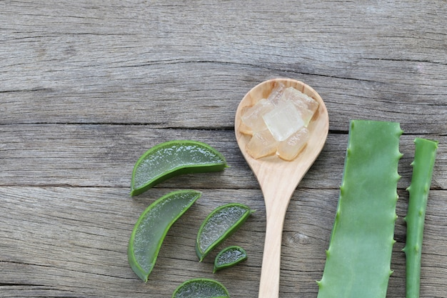 Aloés fresco cortado vera na colher de madeira no assoalho de madeira marrom.