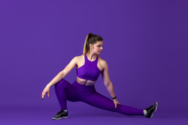 Alongamento. bela jovem atleta praticando, retrato roxo monocromático. treinamento esportivo do modelo de ajuste caucasiano. musculação, estilo de vida saudável, conceito de beleza e ação.