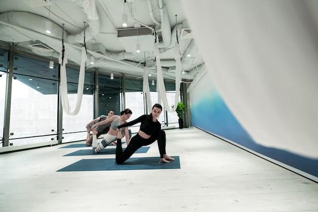 Alongamento e ioga. duas mulheres magras e em forma e um homem esticando as pernas enquanto praticam ioga