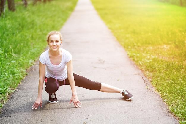 Alongamento mulher fitness no parque de verão. retrato de fitness ao ar livre