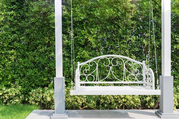 Alpendre com um balanço de alpendre branco no jardim em casa.