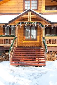 Alpendre decorado de uma mansão de madeira de natal coberta de neve