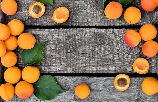 Alperces maduros deliciosos em uma tabela de madeira rústica. frutos crus no fundo de madeira áspero. comida vegetariana. vista de cima