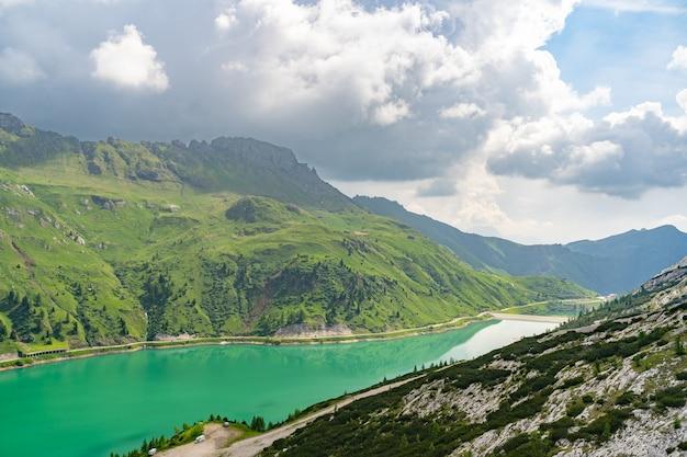 Alpes idílicos com colina verde e rio