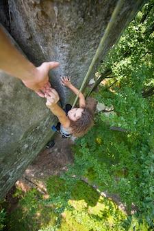 Alpinista ajudando alpinista feminina para chegar ao topo da montanha