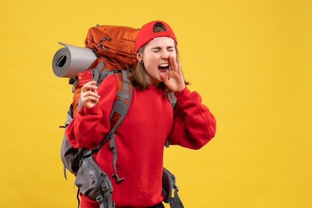 Alpinista bonita de frente para mulher com mochila segurando cartão de crédito gritando