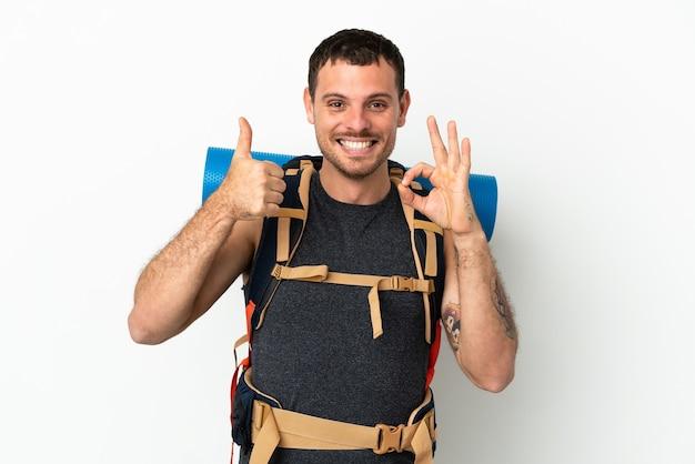 Alpinista brasileiro com uma mochila grande sobre fundo branco isolado, mostrando sinal de ok e gesto de polegar para cima