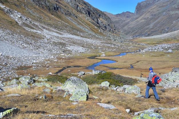 Alpinista caminhando em um prado atravessado por um rio na montanha rochosa alpina