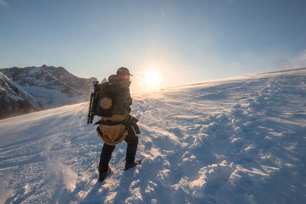 Alpinista caminhando na colina de neve até o topo da montanha com o sol brilhando ao pôr do sol
