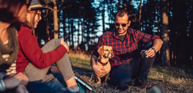 Alpinista com amigos e seu cachorro descansando e tomando café