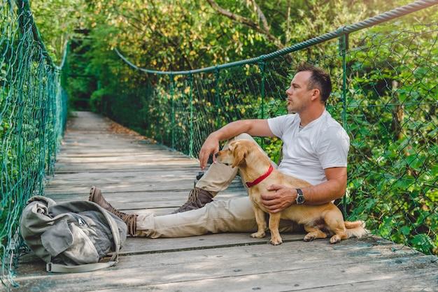 Alpinista com cachorro descansando na ponte pênsil de madeira