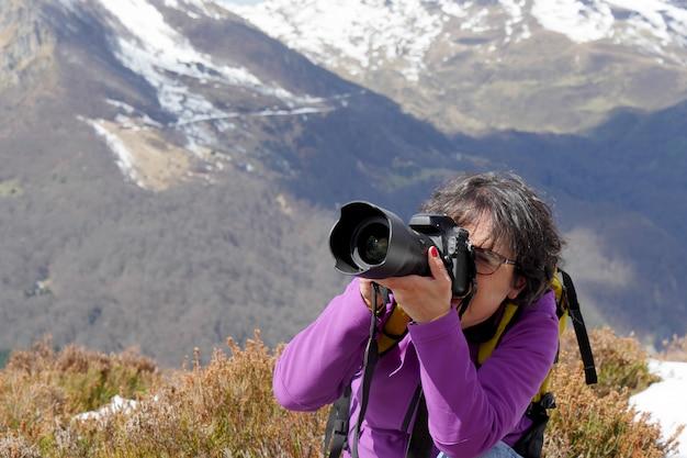 Alpinista com câmera e mochila, tirando foto da bela montanha