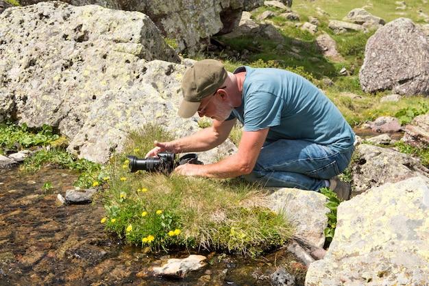 Alpinista com câmera tirando foto de pequeno fluxo
