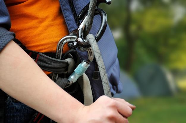Alpinista com equipamento para escalada (mosquetão e corda)