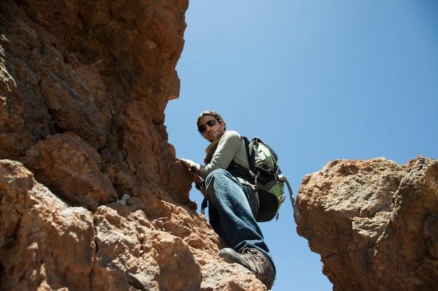Alpinista com mochila escalando rochas