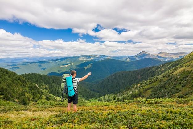 Alpinista com uma mochila em pé nas montanhas