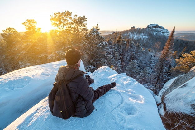 Alpinista com uma mochila sentado no topo de uma falésia nas florestas da sibéria ao pôr do sol