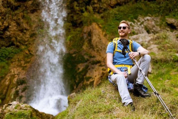 Alpinista de cabelo vermelho jovem bonito parou ao lado de uma cachoeira de montanha para descansar