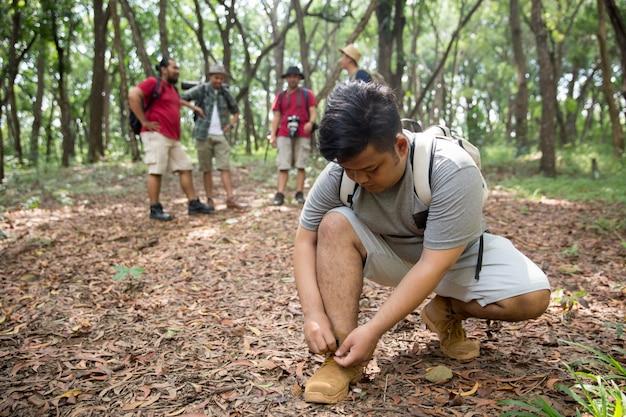 Alpinista de homem, amarrando os sapatos