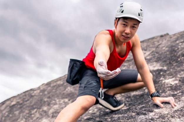 Alpinista de homem asiático em calças pretas, escalar o penhasco e dar a mão para ajudar o amigo.