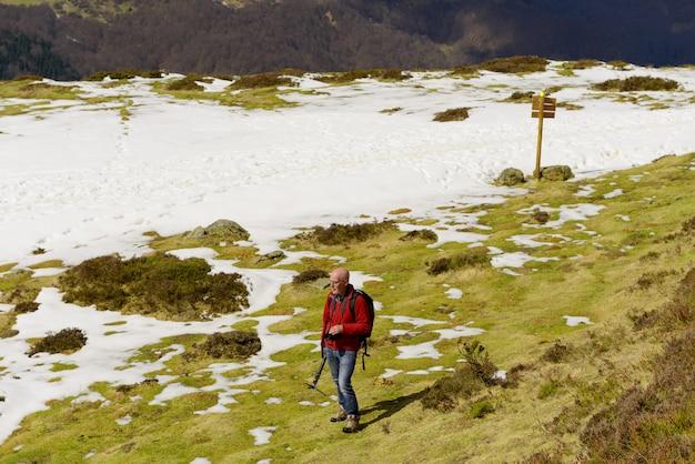 Alpinista de homem maduro com mochila na montanha