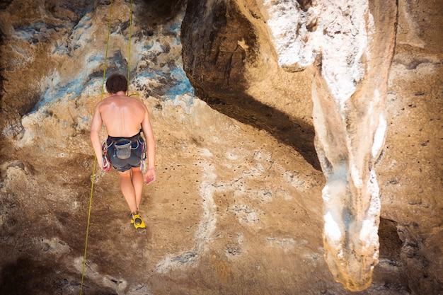 Alpinista de homem pendurado no penhasco com uma corda. descansando no ar