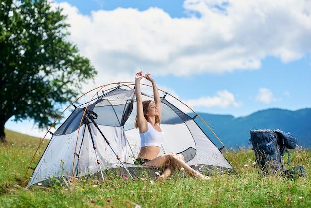Alpinista de menina bonita sentada na tenda ao lado de mochila e bengalas, no topo de uma colina, sorrindo, levantando as mãos no ar, aproveitando o dia ensolarado com os olhos fechados nas montanhas