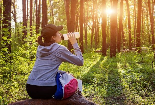 Alpinista de menina com mochila bebe água na floresta