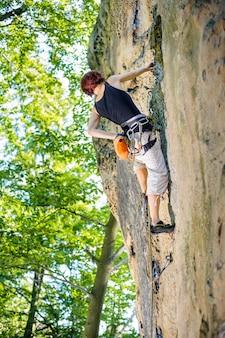 Alpinista de menina subindo com corda e carabinas na pedra grande