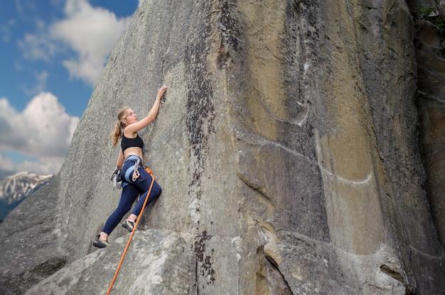 Alpinista de menina subindo com corda e mosquetões em uma pedra grande