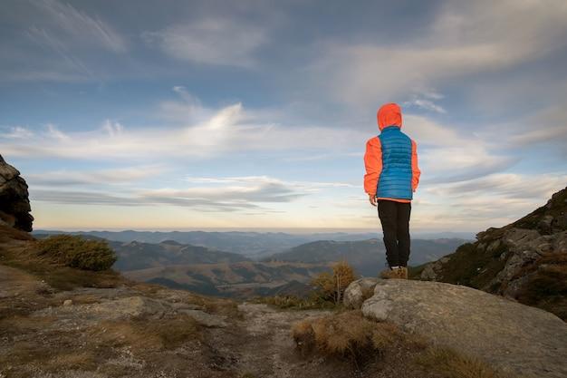 Alpinista de menino jovem criança em pé nas montanhas, apreciando a vista da paisagem de montanha incrível.