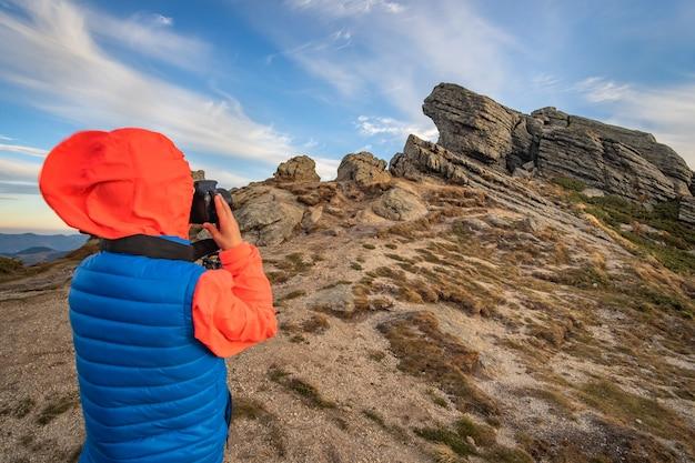 Alpinista de menino jovem criança tirando fotos nas montanhas, apreciando a vista da paisagem de montanha incrível.