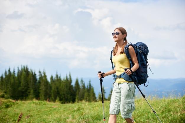 Alpinista de mulher andando na colina gramada