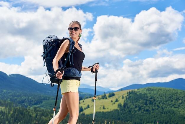 Alpinista de mulher bonita sorridente, caminhadas na trilha de montanha dos cárpatos, usando varas de trekking, aproveitando o dia ensolarado de verão nas montanhas. conceito de turismo