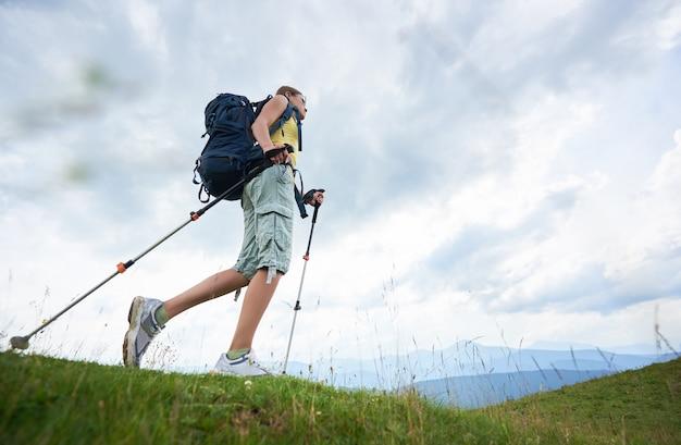 Alpinista de mulher caminhadas na colina gramada, usando mochila, usando bengalas nas montanhas
