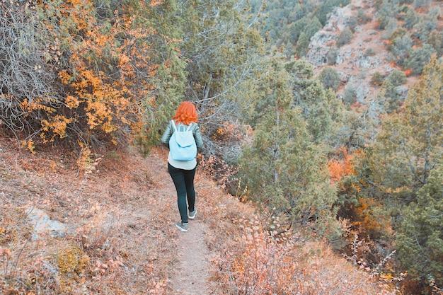 Alpinista de mulher com mochila andando na floresta de montanhas.