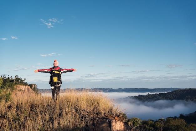 Alpinista de mulher com mochila no topo da montanha com os braços abertos.