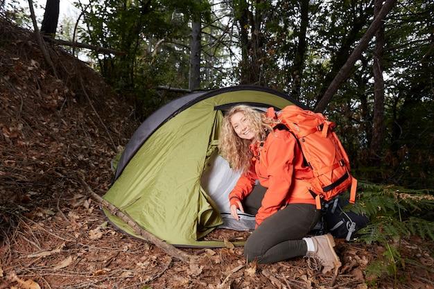 Alpinista de mulher com tenda na floresta