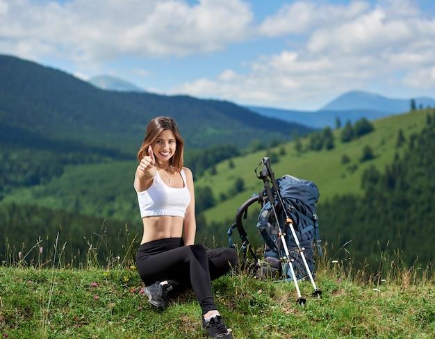 Alpinista de mulher feliz com mochila e bastões de trekking, sentado no topo de uma colina, mostrando os polegares, descansando depois de caminhadas, aproveitando o dia de verão nas montanhas