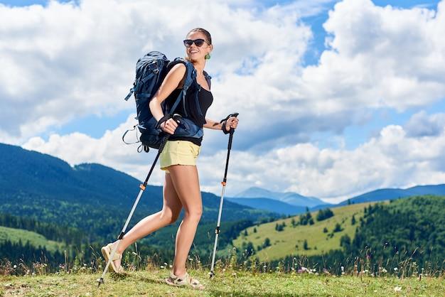 Alpinista de mulher feliz magro caminhadas trilha de montanha, andando na colina gramada, aproveitando o dia ensolarado de verão nas montanhas