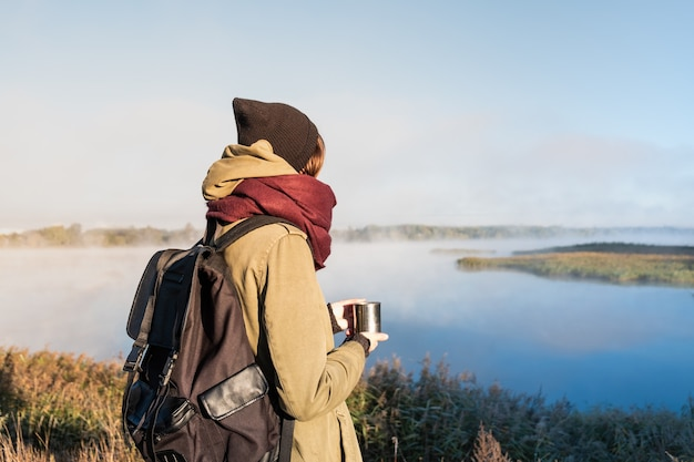 Alpinista de mulher gosta de belas paisagens naturais com um copo de bebida quente. jovem fêmea tomando café e admirando o lindo rio coberto de névoa.
