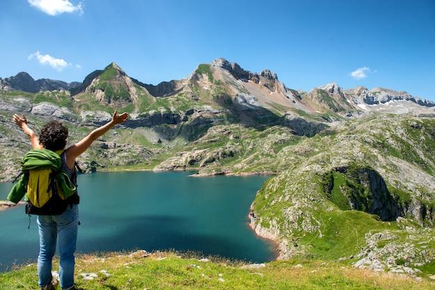 Alpinista de mulher olhando para o lago estaens nas montanhas dos pirenéus