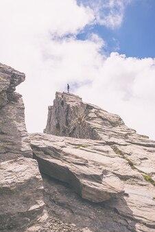 Alpinista de pé no pico da montanha, imagem enfraquecida