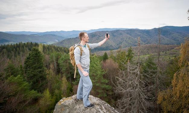 Alpinista de pé no pico de uma pedra e faz selfie no seu telefone